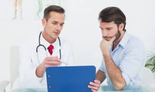 Male doctor discussing reports with patient at desk in medical o